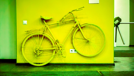 decoration in office. acid green bicycle as decoration and power socket and switch on the wall. old painted bicycle attached to the wall in art office. vintage bicycle on decorative color wall Stock Photo