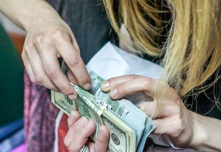 large group of business people: how to check dollar. dollar in hands. women or man ounts dollar bills and get it into the light ivory grey table. Pile of new and old one hundred dollar bills.