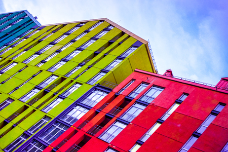 high burgundy yellow violet multi-storey houses stay one by one as place for people family live against blue sky with white clouds. Colourful multi-storey residential building above blue sky Stock Photo