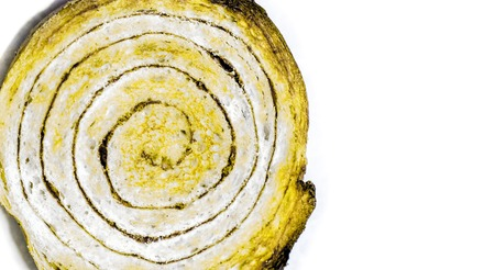 close up of cut round cinnamon bun with dark spiral and texture of a porous dough inside with dark brown crispy crust. bun as sweet fresh snail on white background