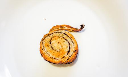 cut cinnamon bun on white background