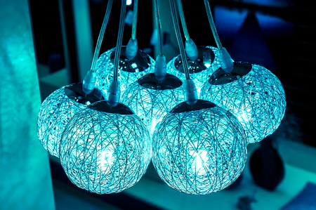 chandelier background: crystal bright blue lightning balls. modern art luxury chandelier made with balls with lamp inside every one, which connect to beautiful blue flower. Lighting ball hanging from ceiling on background Stock Photo