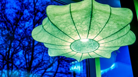 emerald green chandelier with light inside as umbrella against black background. umbrella lamp hangs his cane up as decoration of modern night club. Lighting umbrella shape from small lamps at night Stock Photo