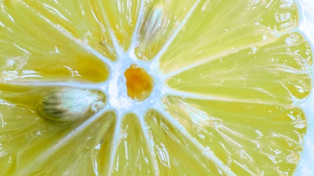 central circle of juicy yellow organic sweet fresh lemon slice with white circle in the center, diagonal white lines to the skin and few small ivory seeds inside it. texture of fresh lemon lobule. Stock Photo