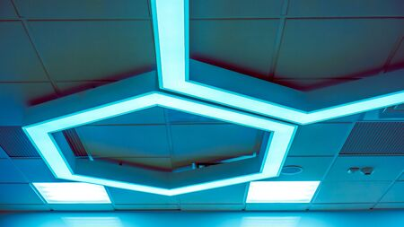 chandelier background: few big blue hexagons with light inside is on ceiling with classic office squares in Modern Design Studio, large hexagon chandelier against geometric ceiling as a decor modern element