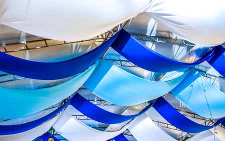 openspace: blue ribbons waves. colorful ribbon decoration on ceiling at beer festival. typical decoration at a oktoberfest. ribbons rainbow as ceiling decoration in openspace or bar or restaurant