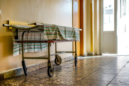 critical care: Wheelchair wait for visitors and ill people in corridor of city hospital. Wheelchair as symbol of last way. Social hospital for poor man. Interior of old city municipal hospital.
