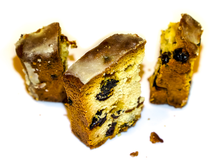 isolate three small peaces of holiday cake with raisins and other dried fruits surrounded by crumbs against white background. Christmas Stollen on a white plate