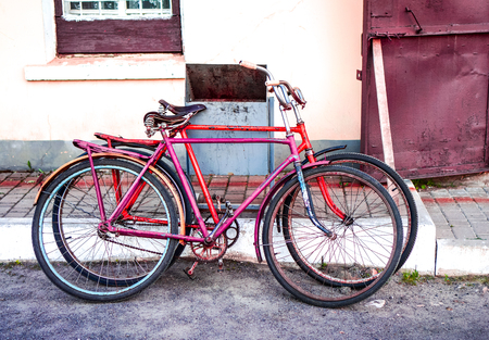 two old vintage bicycles pink and red parking near ivory yellow building in hot sunny day. Vintage bicycle in rack, on the street parking, close up. Transportation concept