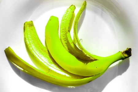 banana skin: green bright banana skin without ripe inside lay on white plate as human five fingers. banana skin isolated on white background in sunshine