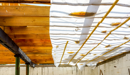 wooden horizontal planks with metal pylons and white walls on the future roof of country house in sunshine. the interior of the frame house in process of construction village