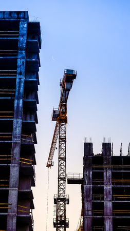 alone crane between buildings against sunset sky. big high crane under a new construction site of high-rise building against blue sunset sky. lonely metal cranes bottom view Stock Photo