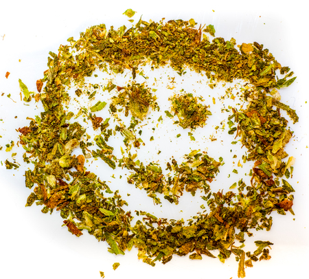 be happy with cannabis. make me smile with cannabis green grass. smiled smile made by dry cut green cannabis before using. Marijuana Bud Cannabis Close Up On white background