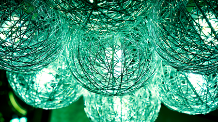 expensive: small lamps inside green lightning balls. modern art luxury chandelier made with balls with lamp inside every one, which connect to beautiful flower. Lighting ball hanging from ceiling on background