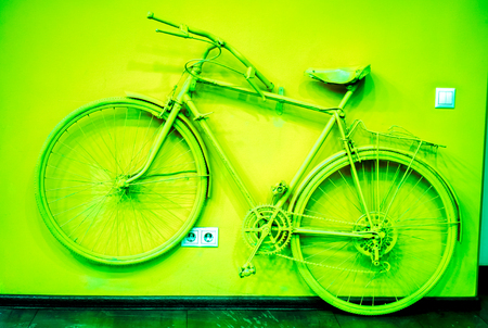 wall socket: power socket and switch on the wall with emerald green bicycle as decoration. old painted bicycle attached to the wall in art office toned to green color. vintage bicycle on decorative color wall Stock Photo