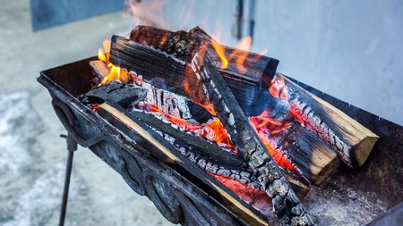 white frozen ground and black braizer with hot bright spurt of flame illuminate twilight and warm everything near. Flames fire. Preparation for cooking barbecue. fire flame texture as natural back Stock Photo