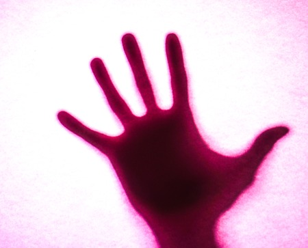 creepy alien: pink light on mans hand as actor of shadow theatre. Hands shadow as figure of dinasaur. Shadow hands of the Man behind frosted glass. Blurry hand abstraction. Halloween background.