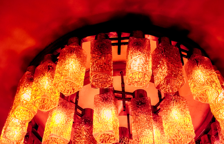 many fire yellow orange decorative modern shaped lamps on ceiling against dark background, many modern ceiling lamps with abstract ornament as luxury chandelier Imagens