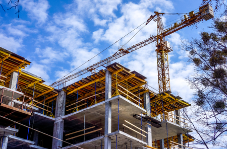high building crane and new future building with yellow planks above blue sky. Stock Photo