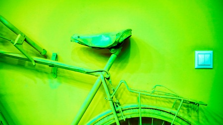small light socket near acid green part of wheel, part of frame and saddle as part of old painted bicycle used for decoration in office. vintage bicycle on decorative color wall in art office