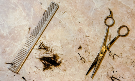 top view to open silver hair cutting shears and vintage metal steel comb against small spots of dark cutting hair and many small filaments on the table after haircut. Work still life of hairdresser Stock Photo