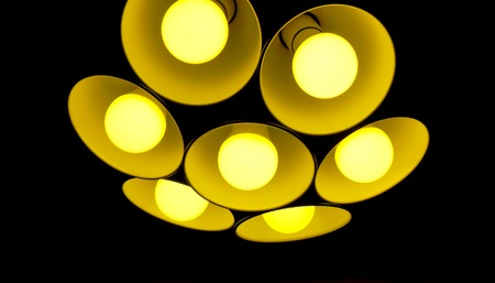golden yellow flower made from lamps as modern chandelier with seven round plafonds with lamps inside them against black background. electric fixture with round plafonds from glass Stock Photo