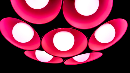 modern crimson red pink art chandelier with seven round plafonds with lamps inside them against black background. Minimalistic chandelier as flower. electric fixture with round plafonds from glass