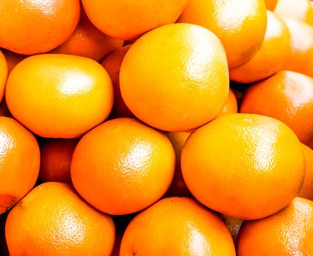 sunshine on many circle orange ripes lay one by one as background. texture of orange ripes
