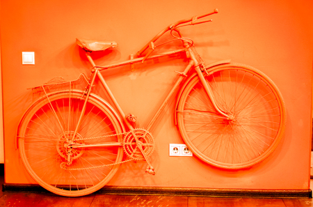 vintage bicycle toned to acid orange color and connect to wall as decoration near power socket and switch. old painted bicycle in art office tone to orange color. vintage bicycle on color wall Stock Photo