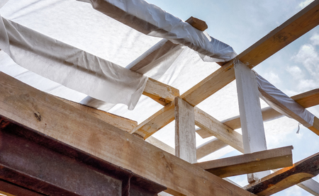 wooden horizontal and vertical planks on the future roof of country house in sunshine against blue sky. the interior of the frame house in process of construction village Фото со стока
