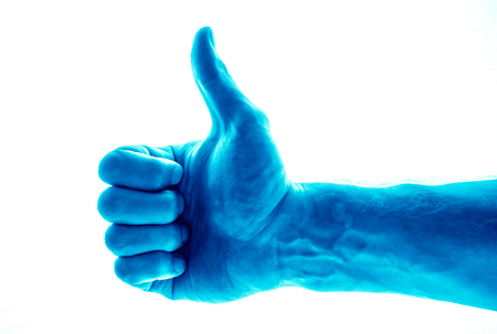 Like concept. Voting hand on blue background. One hand making thumb up gesture. toned to deep blue mans hand as facebook like hand