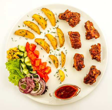 Grilled bekonwith roasted potato peaces, fresh tomatos, onion, cucumber, salad and red sous against white round plate isolate. delicious food with meat and vegetables on white plate Stock Photo
