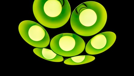 lamp shade: bright modern green emerald chandelier with seven round plafonds with lamps inside them against black background. electric fixture with round plafonds from glass Stock Photo