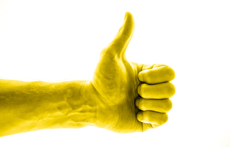 Voting hand on white background. One hand making thumb up gesture. like hand show success toned to golden yellow