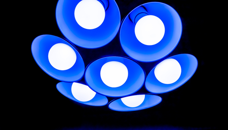 lamp shade: bright big flower modern blue chandelier with seven round plafonds with lamps inside them against black background. electric fixture with round plafonds from glass