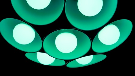 lamp shade: modern green emerald chandelier with seven round plafonds with lamps inside them against black background. electric fixture with round plafonds from glass