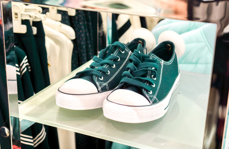 top view to green sneaker shoes wait for its master in sale season in big fashion shop. dark blue sport shoes with round white security magnet tag stay on white high shelf against modern clothes