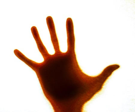 red light on mans hand as actor of shadow theatre. Hands shadow as figure of dinasaur. Shadow hands of the Man behind frosted glass. Blurry hand abstraction. Halloween background.