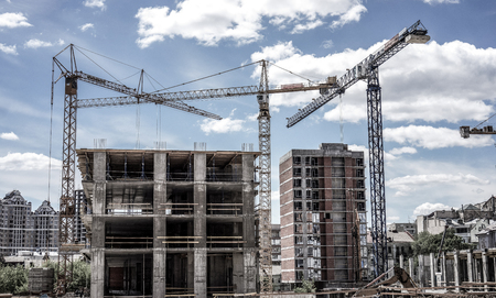 Three high cranes under one building multistorey building against green trees, business centres and blue sky. Industrial Building with Copy Space. Cranes Building New House on the Construction Site. Stock Photo