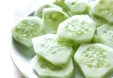 cucumbers: many light green fresh cucumber circles on plate ready for eating. Fresh Cucumber and slices on white plate