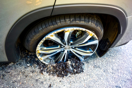 the cars drive burrowed into the asphalt as a result of car crash top view. silver luxury car wheel inside road asphalt. Round Damaged vehicle closeup after car crash. Stock Photo