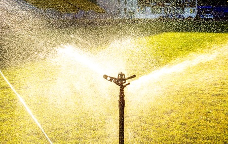 to maintain: Automatic lawn watering on big field in sunshine and shadows. lawn watering as wings made of water drops. Garden sprinkler on a sunny summer day during watering the green lawn Stock Photo