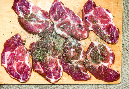 few raw meat peaces with spices, salt and black peppercorn. raw peaces of ham on wooden desk. spiced meat as future tasty meal as beef Stock Photo