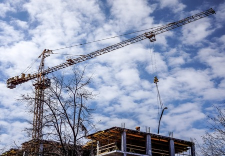 residential: yellow high building crane and new future building with yellow planks above blue sky with white clouds. Construction of a new multi-storey house near tree against blue sky on a sunny day Stock Photo