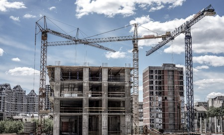 residential: Three high cranes under one building multistorey building against green trees, business centres and blue sky. Industrial Building with Copy Space. Cranes Building New House on the Construction Site. Stock Photo