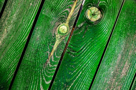 grass green emerald diagonal old wooden planks with parts of cracked paint, knots and spots as wooden texture. vintage wooden planks as background