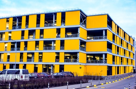 big multi store parking building for many cars in housing complex. Yellow home for many cars against blue sky and few cars near Stock Photo