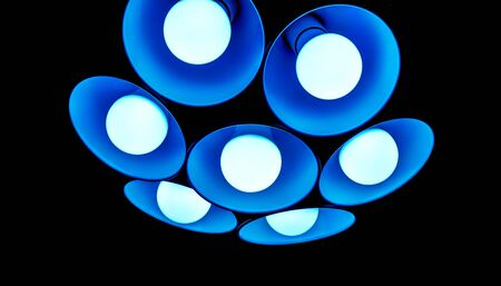 them: bright big flower modern blue chandelier with seven round plafonds with lamps inside them against black background. electric fixture with round plafonds from glass