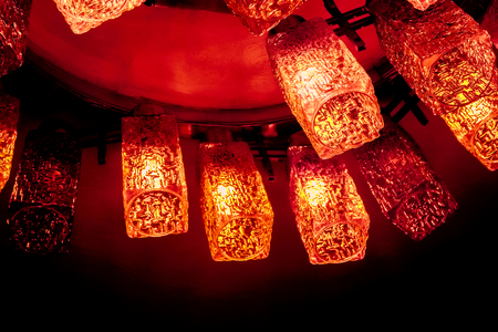 top view to part of crimson round decorative modern shaped lamps on ceiling against dark background, many modern ceiling lamps with abstract ornament