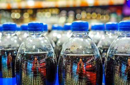army of plastic bottles with black liquid and navy blue covers stand in strong rows at shop and wait for buyers.